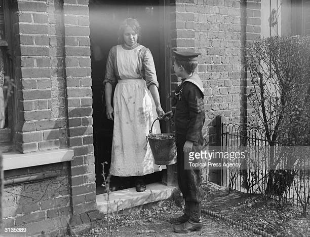 Naval cadet collecting food for pigs at a house in Ilford, Essex.