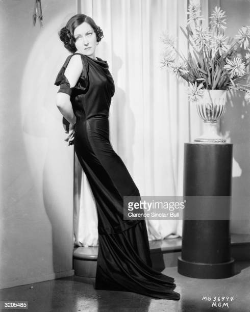 American actress Gloria Swanson wearing a clinging floorlength evening dress with slit sleeves