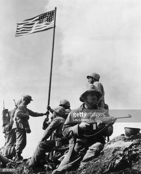 American soldiers raise the first US flag atop Mount Suribachi in Iwo Jima Japan
