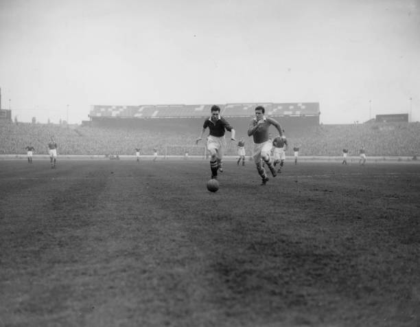 Chelsea centre forward, Jim Lewis, competes with a defender for the ball, as Chelsea play Charlton Athletic at Stamford Bridge.