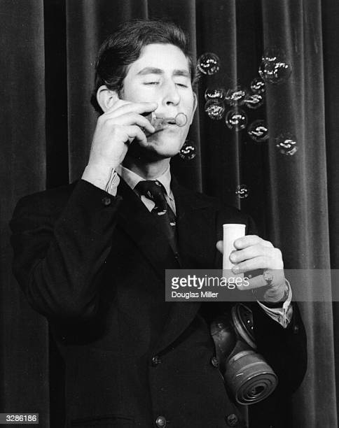 Charles Prince of Wales starring in the Trinity College Cambridge annual revue 'Quiet Flows The Don' He blowing bubbles during a parody of weather...