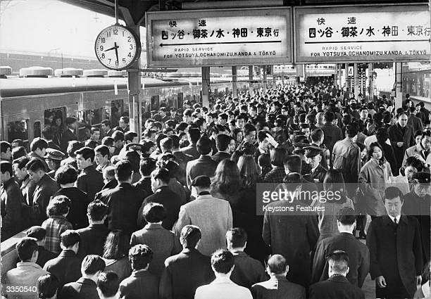 Morning crowds at Shinjuku railway station during peak hour travel A white gloved guard answers a question