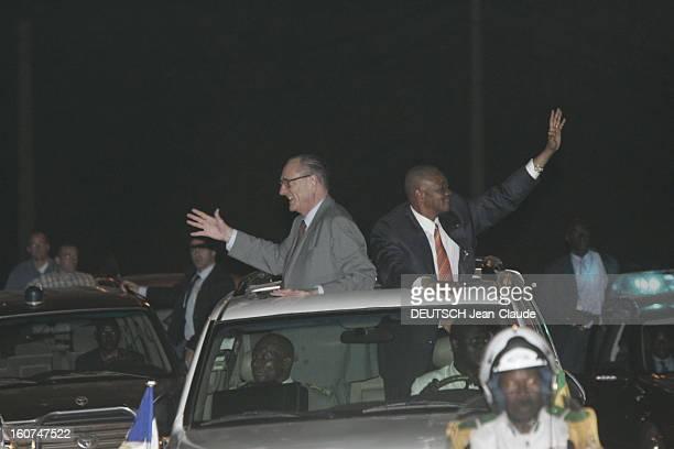 23rd Franceafrica Summit Attitude souriante de profil de Jacques CHIRAC et Amadou TOUMANI TOURE dos à dos debout dans une voiture salués par la foule...