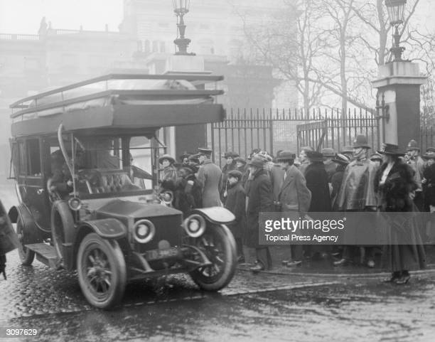 A RollsRoyce at the gates of Buckingham is adapted to be driven by gas to save petrol in WW I The crowds are there for the investiture of VC's DSO's