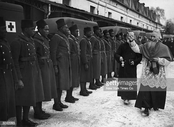 Soldiers from the French colony of Indochina line up as a Catholic priest Monsignor Hunsac blesses them during a ceremony in which Indochina bestowed...