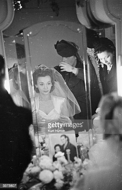American film actress Carole Landis sitting at a mirror in a wedding dress before her marriage to American Airforce captain Thomas Wallace in London...