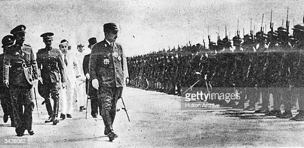 Premier General Hideki Tojo reviewing a regiment of Thai troops. He was the instigator of the attack on Pearl Harbour .