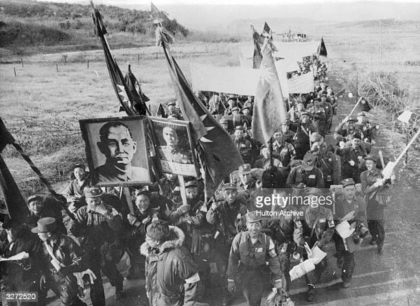 Chinese anti-Communist prisoners of war in Korea marching to freedom, carrying portraits of Chiang Kai-Shek and Sun Yet-Sen, and flags of Nationalist...