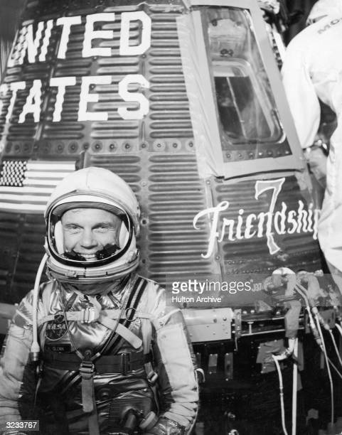 American astronaut John Glenn Jr smiles while wearing a spacesuit and helmet in front of the Mercury Atlas 6 spacecraft 'Friendship 7' Cape Canaveral...