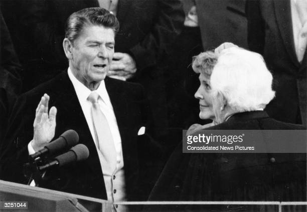 American statesman and former film actor Ronald Reagan the 40th President of the United States takes the presidential oath of office administered by...