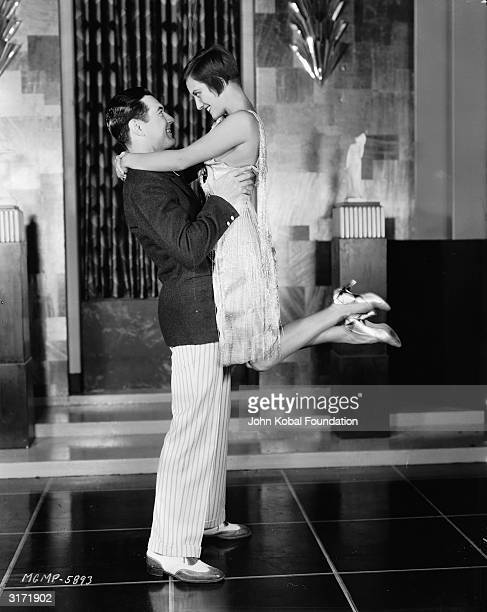 Joan Crawford sets her sights on handsome young millionaire Johnny Mack Brown in the silent film 'Our Dancing Daughters' directed by Harry Beaumont