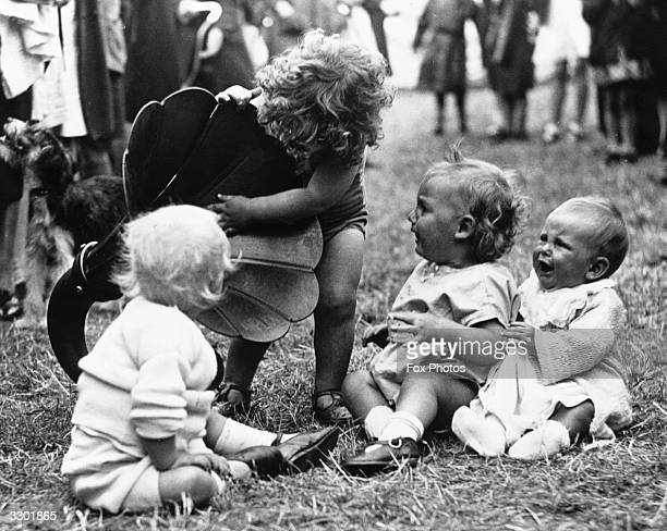 A toddler and three babies who are contestants in a baby show investigating a loudspeaker at the annual Carnival at Fishponds Bristol