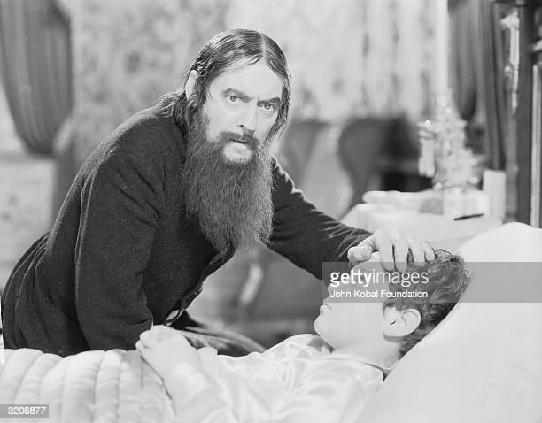 Lionel Barrymore as Rasputin feels the forehead of Tad Alexander as the young Prince Alexis in 'Rasputin and the Empress' directed by Richard...