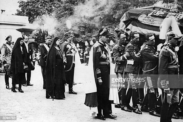 The coffin of Queen Marie of Romania being carried through Bucharest Following it are King Carol II his sister Elisabeth the exQueen of Greece Prince...