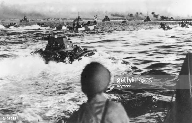 Amphibious tanks of the American army approaching an island beach during the Pacific offensive The island is wreathed in smoke from a preinvasion...