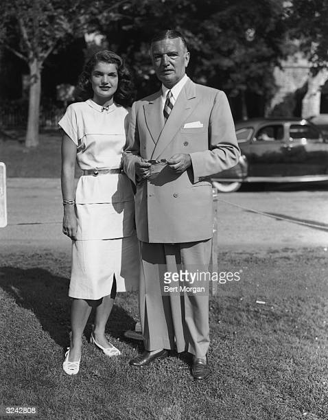 Full-length portrait of Jacqueline Bouvier standing on a lawn with her father, John V Bouvier III , while he holds a pair of sunglasses, East...