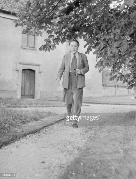 Author Sir Compton MacKenzie walking down a garden path.