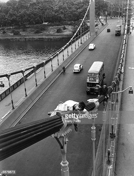 Foreman Len Gilbert and Micahel Gibney, work high above the road and River Thames as they renovate the Chelsea Suspension Bridge.
