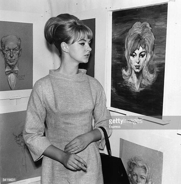 Mandy RiceDavies stands next to a portrait of herself at an exhibition by her associate Stephen Ward