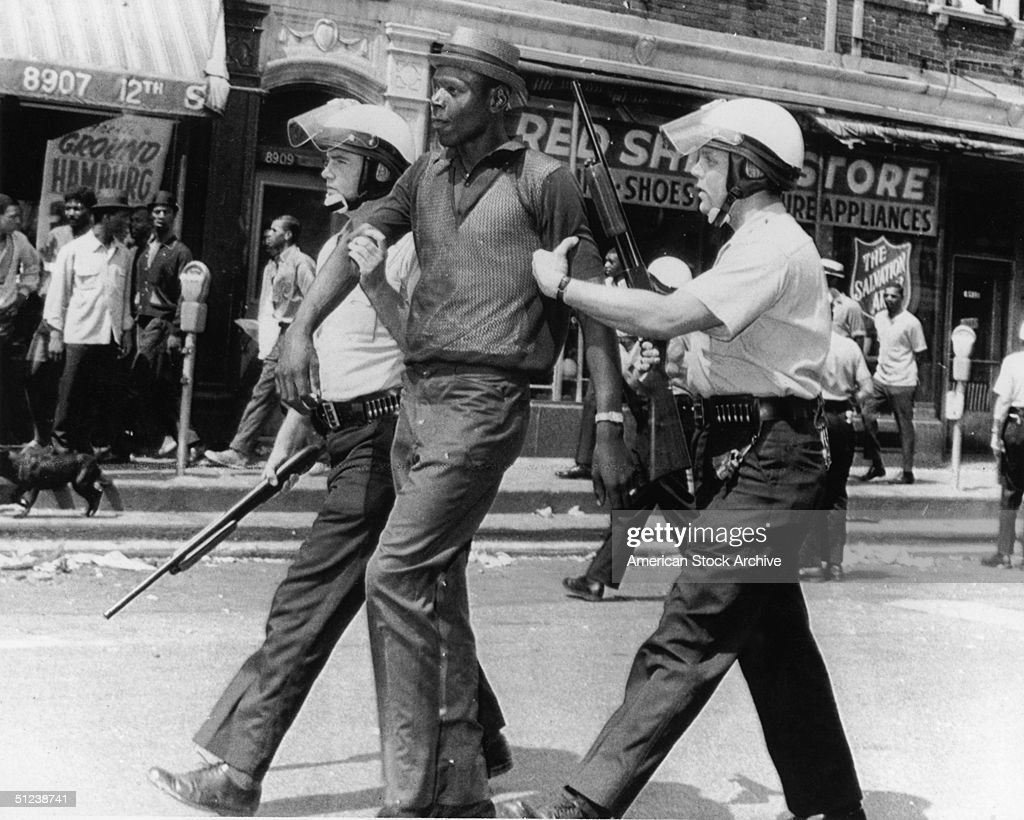 23rd July 1967, Police in riot gear escort an African-American man who they said had been looting after rioting and looting broke out on the west side of Detroit, Michigan.