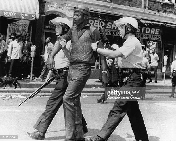 23rd July 1967 Police in riot gear escort an AfricanAmerican man who they said had been looting after rioting and looting broke out on the west side...