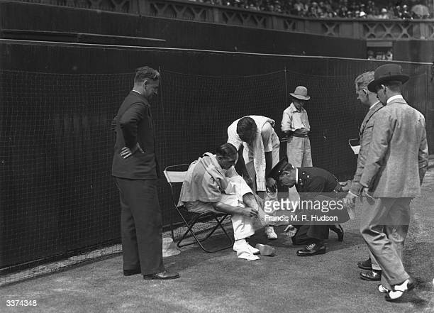 Tennis player E D Andrews having his foot strapped up after an incident during his match against Frank Shields on Wimbledon's centre court