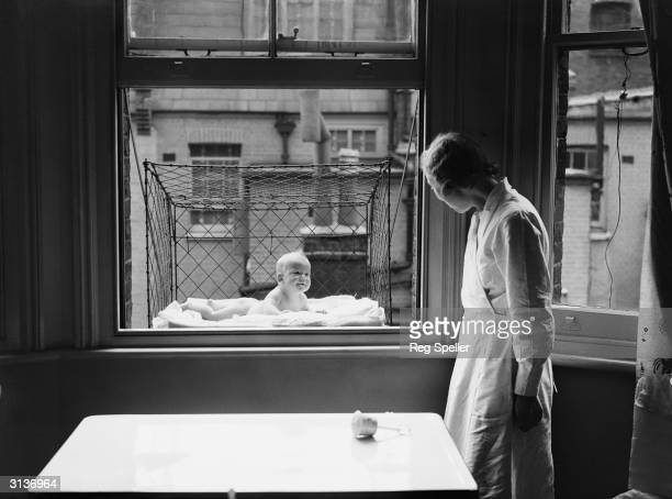 A nanny supervising a baby suspended in a wire cage attached to the outside of a high tenement block window The cages are distributed to members of...