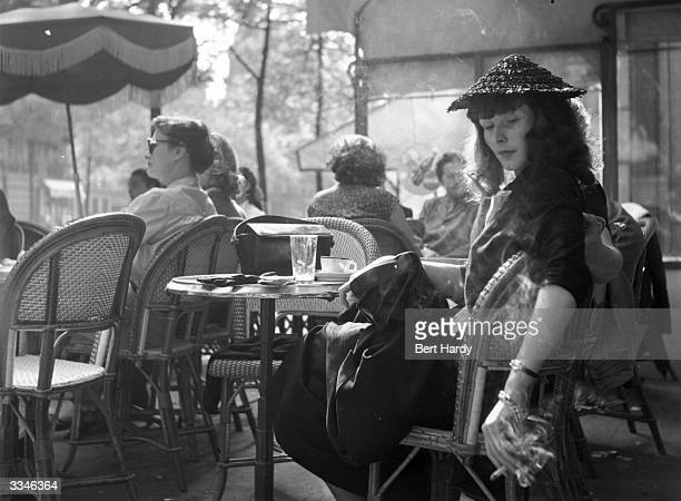 A woman enjoys a cigarette in her favourite cafe on the ChampsElysees Paris Original Publication Picture Post 5343 Sunday Morning In The...