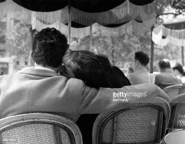 A young couple sharing an intimate moment in one of the pavement cafes on the ChampsElysees Paris Original Publication Picture Post 5343 Sunday...