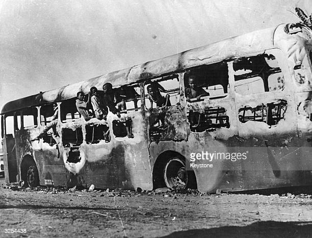 Children play in a burnt out bus following recent rioting in Durban South Africa over the city's measures to clean up the township