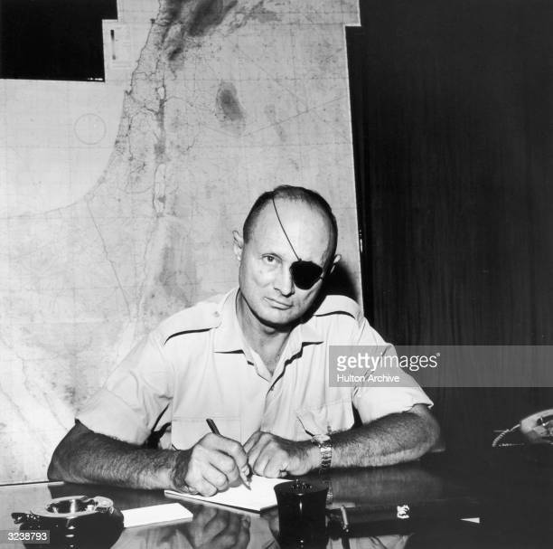 Israeli statesman Moshe Dayan wearing an eye patch and military shirt writes at a desk in front of a map of Israel