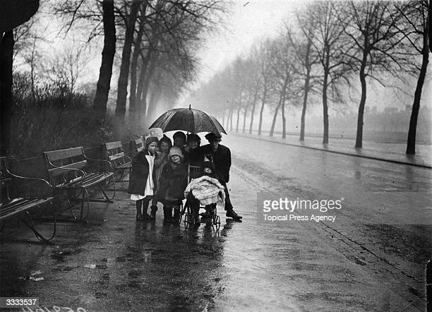 Group of children huddle under a large umbrella, to shelter from the spring rain, in Finsbury Park, London.