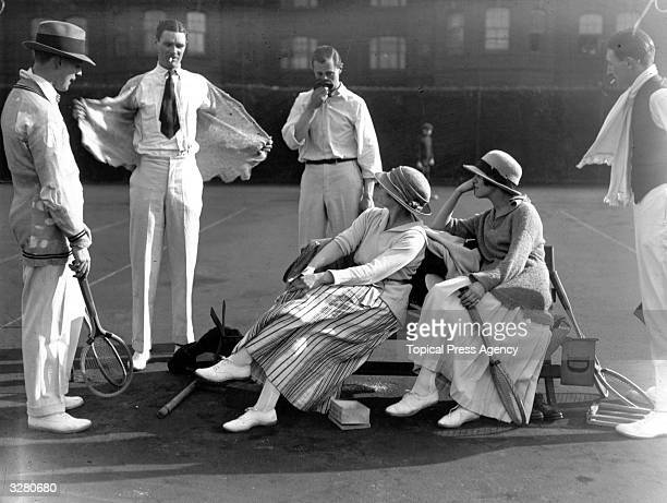 Four men and two women about to enjoy a game of tennis at Queen's Club, London.