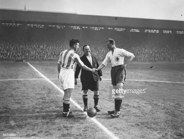 Huddersfield Town captain Wilson shakes hands with Bolton Wanderers captain James Seddon before the start of the FA Cup semifinal match at Liverpool