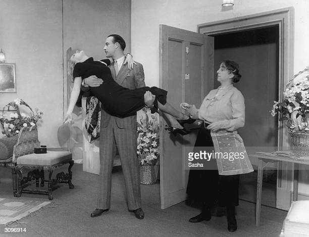 A man lifts a young woman in his arms while an older women looks on unsympathetically in a scene from 'Gay Love' at the Lyric Theatre London