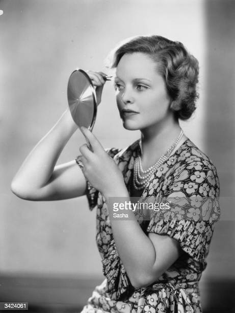Actress Joan Barry plucking her eyebrows
