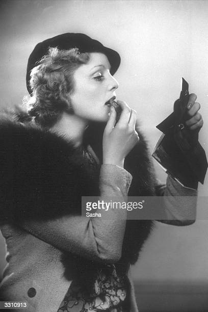 British stage and screen actress Joan Barry applying her lipstick