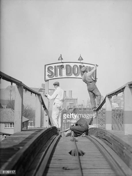 The notice over the scenic railway in Dreamland, an amusement centre in Margate, says 'sit down' but it does not apply to the painters who are...