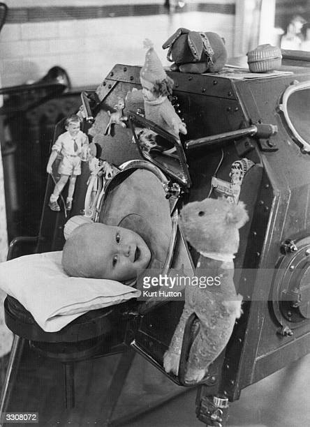 A baby suffering from infantile paralysis having treatment in an 'iron lung' at the Western Fever Hospital Fulham London Original Publication Picture...
