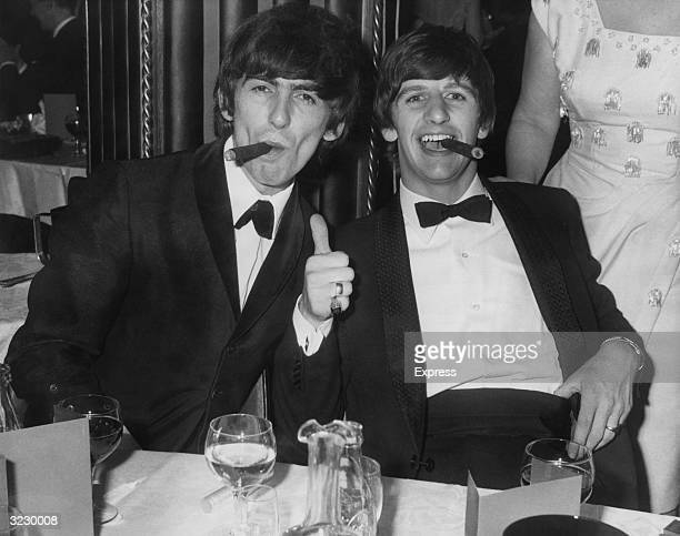 British musicians George Harrison and Ringo Starr members of the rock group The Beatles smoke cigars in tuxedos after the presentation of the Carl...