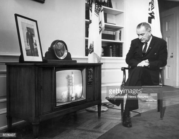 US president Lyndon Johnson watches the launch of the Gemini 3 space capsule on television in his office at the White House Washington DC A framed...
