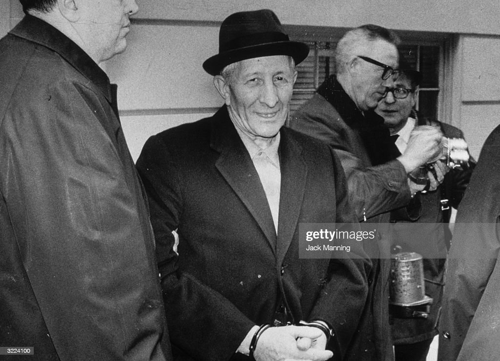 Mob boss Carlo Gambino smiles while standing in handcuffs after being arrested by the FBI.