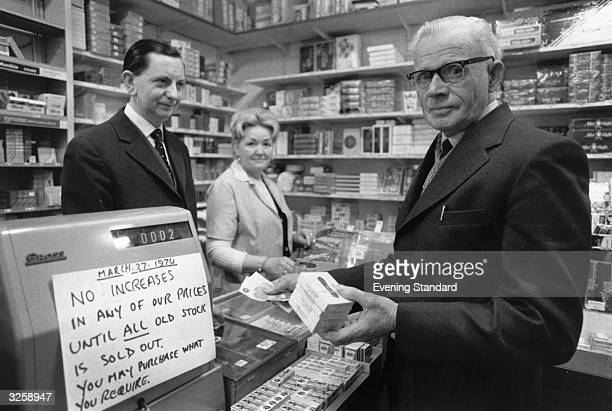 Customer buying cigarettes in a tobacconist in Hatton Garden, London, at the original price, before prices increase.