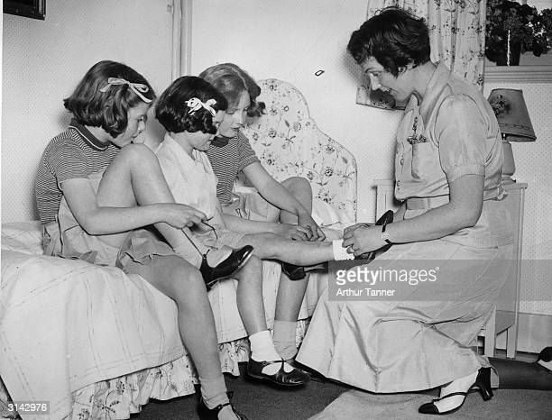 Lady Timothy Eden helps : Tansy Austin and her two daughters, Amelia and Rose Eden, to put on their shoes at Fritham House, Lyndhurst, a school she...