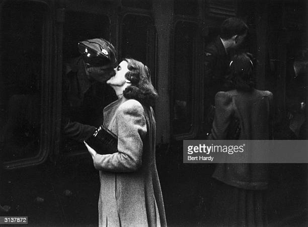 Soldier leans out of a carriage window to kiss his wife goodbye at Paddington station in London. Original Publication: Picture Post - 1133 - War-Time...