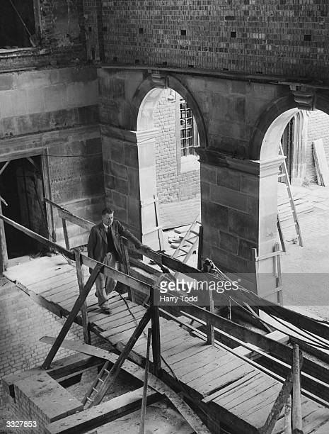 Wooden bridge spans the extensively bomb-damaged Upper School of Eton College, where restoration work is in progress. The roof, walls and floor were...
