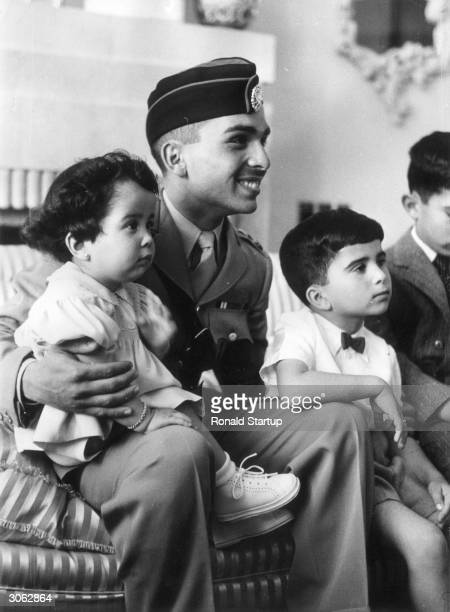King Hussein of Jordan in military uniform after his coronation in Amman. Sitting on his knee is his two year old sister Basma and next to him his...
