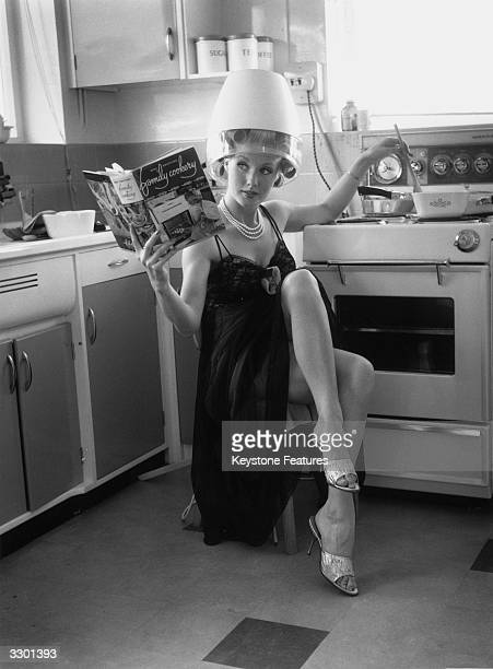 Film actress Barbara Roscoe does the cooking in her spotless kitchen as she waits for her hair to set