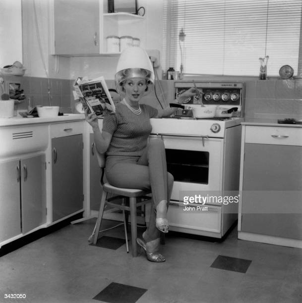 Film glamour girl Barbara Roscoe at home in her kitchen does a spot of cooking while under a hairdryer She is appearing in an Elstree film 'Crooks in...