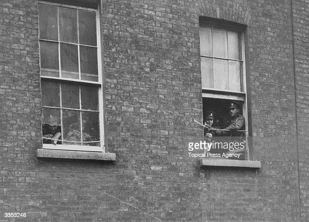 British soldier on sentry duty at a window in Dublin Castle. He is keeping a watch out for Sinn Fein's Irish Volunteers who are waging a guerilla...